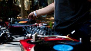 Un DJ usando una mesa de mezclas acompañada de dos platos